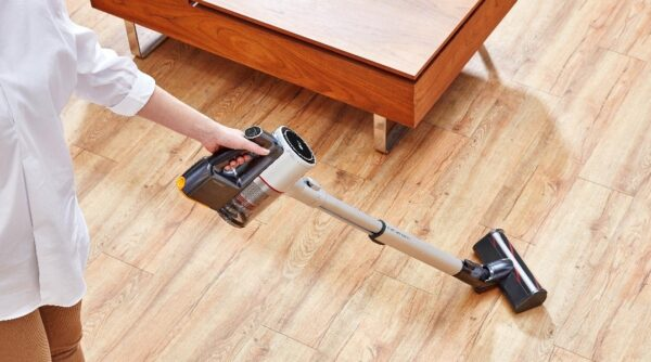 A woman uses the LG CordZero A9 vacuum cleaner to clean the wooden floor.