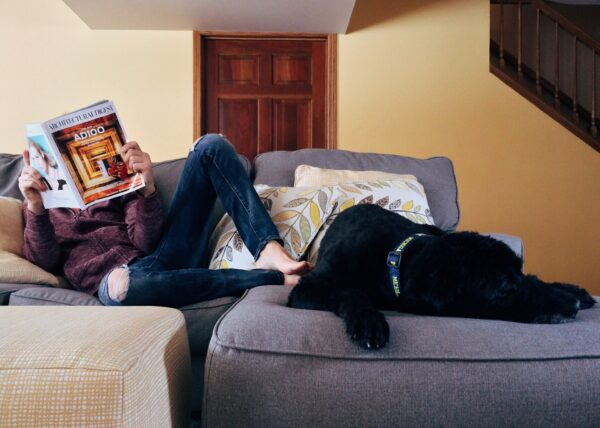 A Man sits on his couch with his dog while reading a magazine.