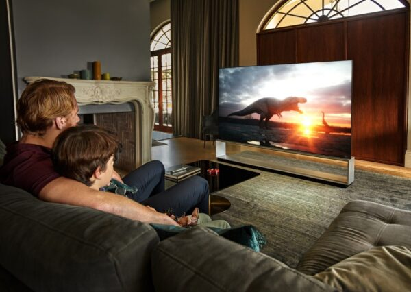 Father and son sit together in their living room to watch dinosaurs come to life on their LG TV.