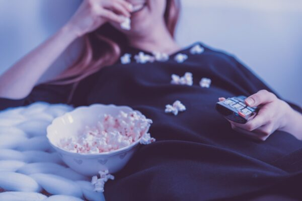 A woman holding the TV remote while eating popcorn.